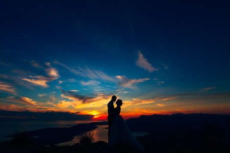 The bride and groom hugging on the top of Mount Lovcen overlooking the Bay of Kotor by the sunset, silhouettes