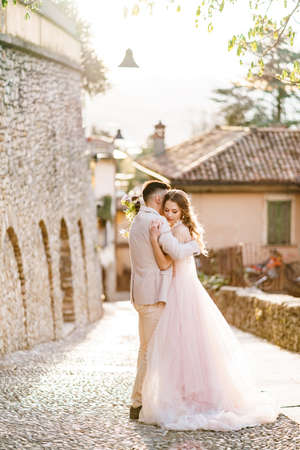 Groom hugs bride in a beautiful dress with a bouquet of flowers on the background of ancient buildings in Bergamo, Italy