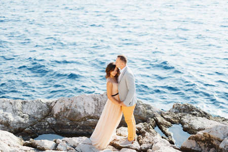 Groom holds the brides hands while standing on the rocks above the blue sea. View from above Banco de Imagens