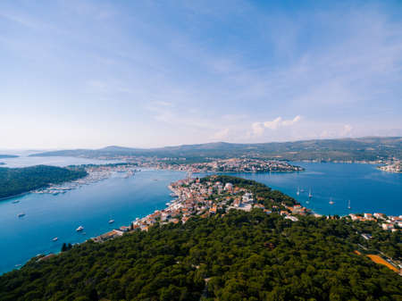 Aerial view of the Adriatic coast, sea, green forest against the blue sky