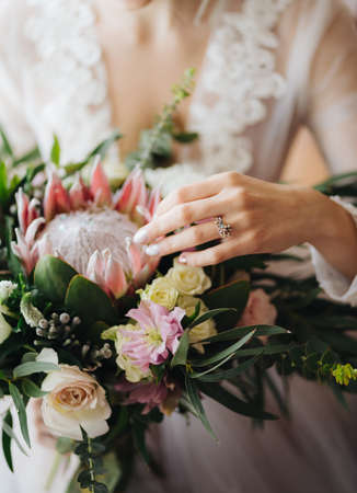 Bride in a white wedding dress strokes a beautiful wedding bouquet. Half portrait
