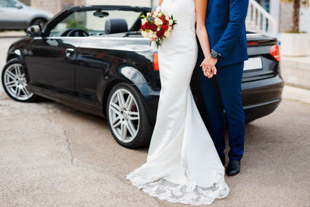 Groom holds the hand of bride with a bouquet of flowers while standing on the paving slabs against the background of a black convertible