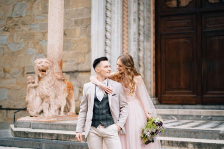 Bride with a bouquet of flowers hugs shoulders of smiling groom on the steps at the entrance to the Basilica of Santa Maria Maggiore in Rome