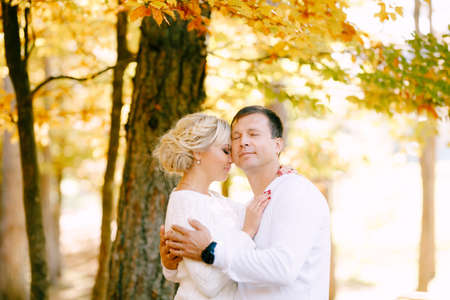 Half-length portrait of a man and a woman in white sweaters hugging against the background of trees in the autumn forest