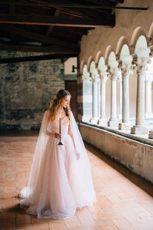 Bride with a burning candle in her hands stands and looks at the floor of the loggia in an old villa on Lake Como
