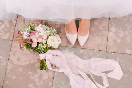 The brides legs in graceful white shoes peek out from under the skirt, next to the brides bouquet lies, close-up
