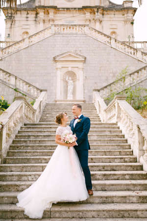 The bride and groom stand hugging on the stairs of the Nativity of the Blessed Virgin Mary church in Prcanj
