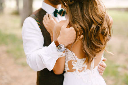 Groom hugs the shoulders of bride in a beautiful embroidered white dress. Bride stands with her back turned