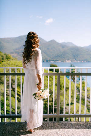 A girl in the long lace robe standing on the balcony overlooking Bay of Kotor on a sunny morning, back view