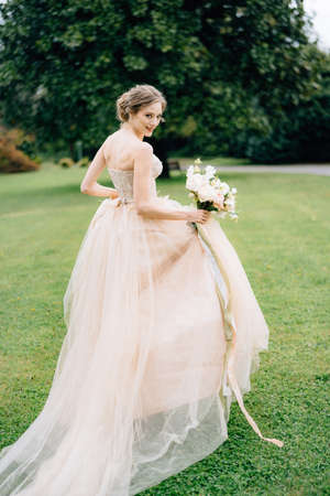 Bride stands with her back turned her head in a pink dress with a bouquet of flowers against the backdrop of a green park. Lake Como. Close up Banco de Imagens