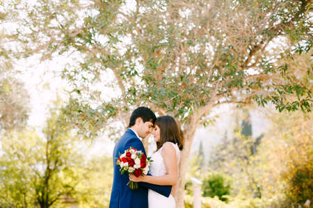 Groom hugs bride in a beautiful white dress with a bouquet of red and pink roses on a green tree background.