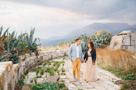 Handsome groom in a bright suit and bride in a leather jacket walk hand in hand through the ruins of an ancient castle