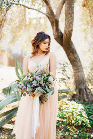 Cute bride in a beautiful dress stands pensively against a tree background with a gorgeous bouquet of flowers in her hands