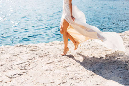 Brides legs in high-heeled sandals and with a fluttering skirt, the bride is walking along the pier, close-up Stok Fotoğraf