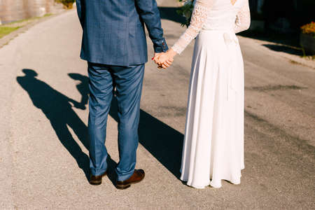 Newlyweds stand on the road holding hands. Sun shines brightly at their back. Silhouettes of bride and groom cast a shadow on the road Stok Fotoğraf