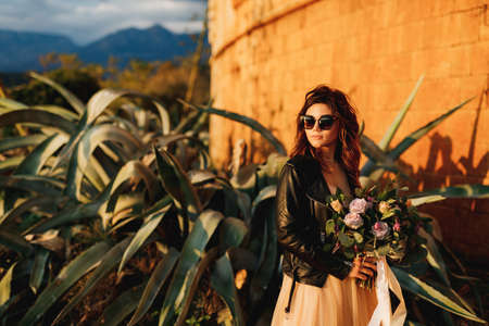 Bride in a beautiful pastel dress and sunglasses holds a bouquet of flowers in her hands against the background of agave bushes and the castle wall