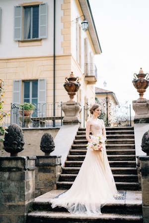 Beautiful bride in a pink dress with a bouquet of flowers stands on the steps of an ancient villa. Lake Como, Italy
