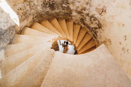 Newlyweds are seen through the spiral staircase of the ancient castle. View from above Banco de Imagens