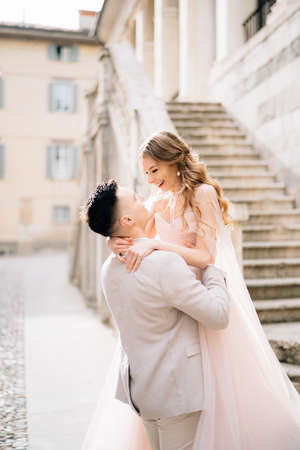 Groom holds bride in his arms near the steps of an old building in Bergamo, Italy. Close up