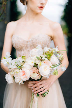 Bride in a beautiful dress holds a bouquet of flowers in her hands