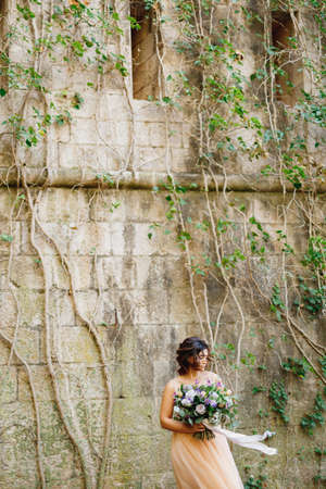 Beautiful bride in a cream wedding dress with a bouquet of flowers on the background of a stone wall on the Mamula island in Montenegro Banco de Imagens
