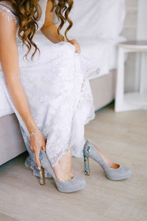 Bride sits on bed and puts on high-heeled shoes in a hotel room while preparing for the wedding ceremony