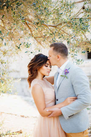 Groom kisses bride in the lovely pastel dress, gently hugging her under the green tree