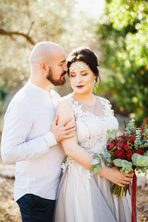 The bride and groom with a bouquet stand hugging among the trees in an olive grove, close-up