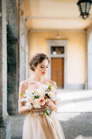 Bride in a beautiful dress with a bouquet of pink flowers stands in an arched corridor. Lake Como, Italy