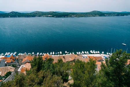 View of the sea and the pier with white yachts from behind the roofs of old houses in Sibenik