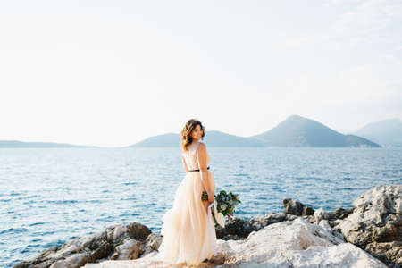 Lovely bride in a pastel wedding dress stands smiling on a rock above the sea with a bouquet of flowers in her hands Banco de Imagens