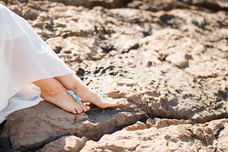 Womans bare feet with elegant pedicure and bracelets on the rocks, close-up. Woman sitting on the rocky beach