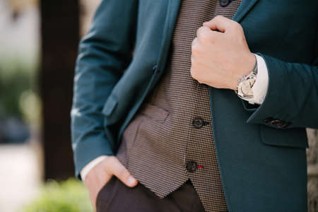 Groom holds his hand on the lapel of a blue jacket Stok Fotoğraf