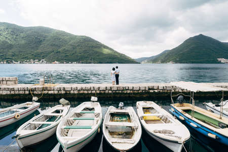 White boats are parked on the dock. Couple is embracing against the backdrop of the mountains and the sea. Perast town, Montenegro Stok Fotoğraf
