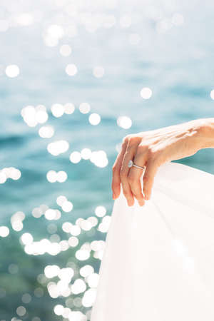Brides hand with a wedding ring on her finger, close-up. The bride holds the edge of the dress against the background of the sea.