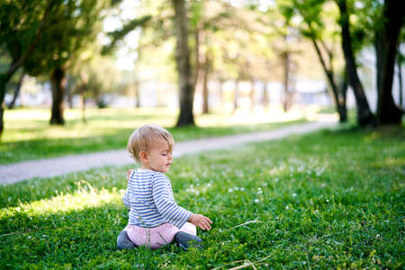 Small child sits on a green lawn near the walkway with his head turned. Back view