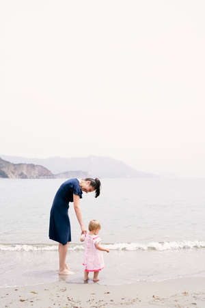 Mom leaned over to the little girl while standing in the water on the beach Banque d'images
