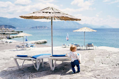 Child stands near a sun lounger on the beach and looks to the side. Back view Imagens