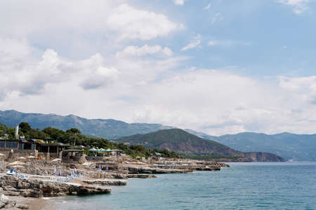 Pebble beach with stone ledges near the sea Imagens
