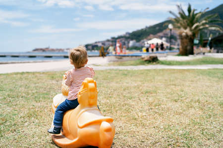 Little child sits on a swing in the playground on the beach and looks at the sea