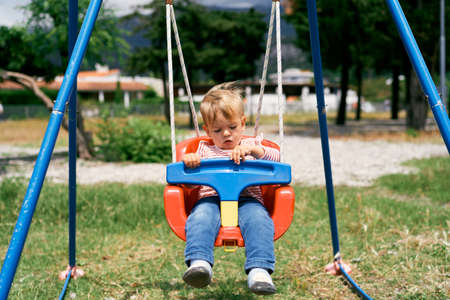 Small child sits on a colorful swing Imagens