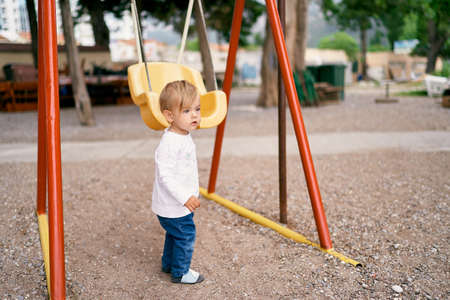 Kid stands on the playground holding the swing with his hand Imagens