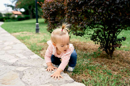 Little girl squatting on green grass in a park near a paved path Imagens