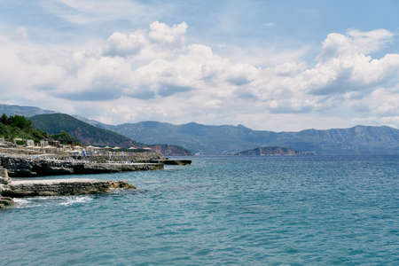 View from the sea to the rocky coast with sun loungers and thatched umbrellas Imagens