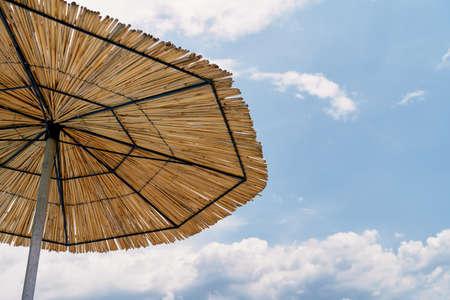 Straw sun umbrella on blue sky background