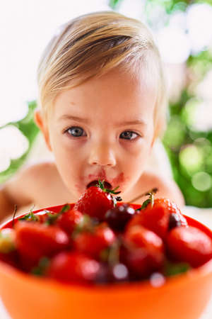 Kid eating strawberries from a bowl of fruit