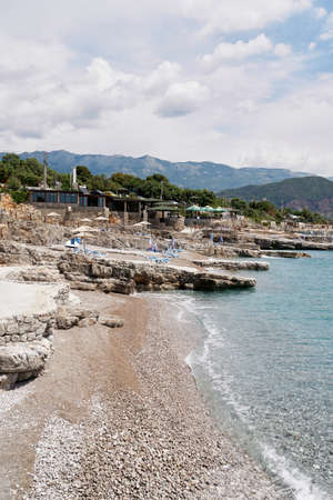 Pebble beach with stone ledges, sun loungers, umbrellas and a small restaurant Imagens