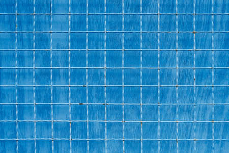 Metal mesh with square cells on blue painted background
