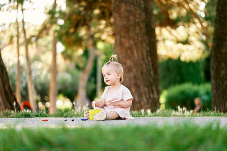 Little girl sits on a path in a green park with a toy bucket in her hands