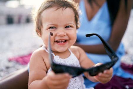 Smiling little girl holding big sunglasses in her hands